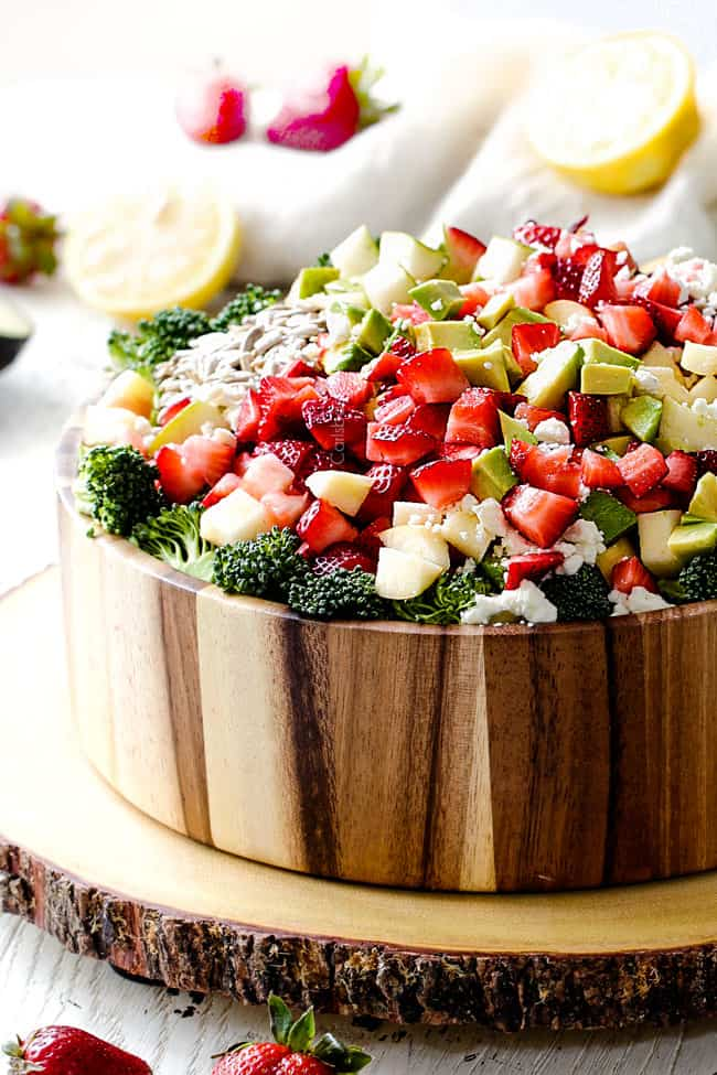 Side view of Best Broccoli Salad in a wood bowl with avocados, strawberries, sunflower seeds, dried cranberries