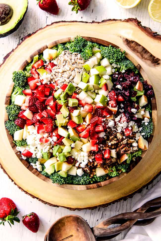top view of best Broccoli Salad in a wood bowl on a wood platter with pears, apples, craisins, avocados, strawberries and creamy dressing