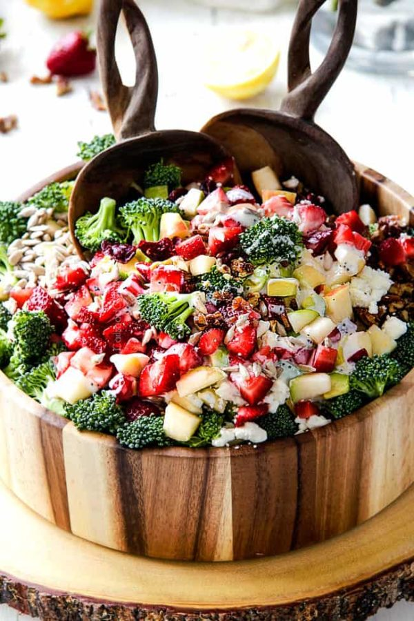 combining best broccoli salad in a wood bowl with wood tongs with creamy dressing