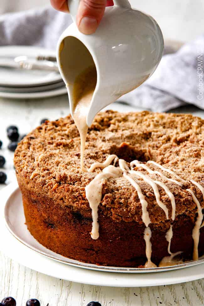 pouring glaze over easy blueberry coffee cake with streusel crumb topping