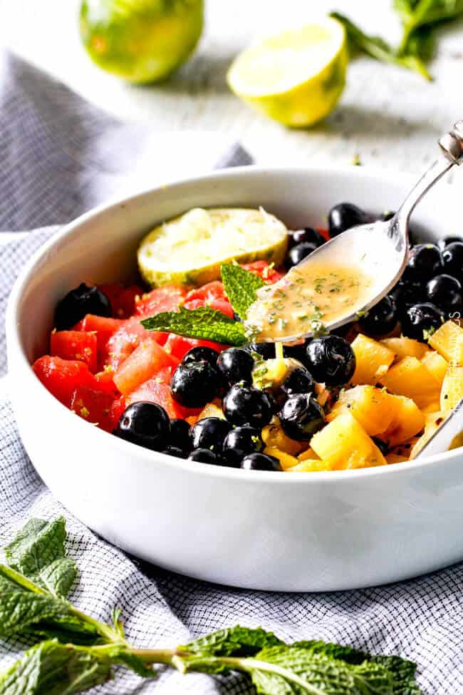 showing how to make summer fruit salad by drizzling on fruit salad dressing