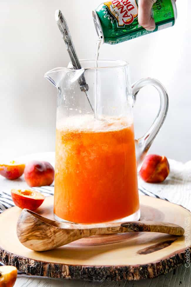 Showing how to make Sparkling Peach Punch by adding Canada dry soda.