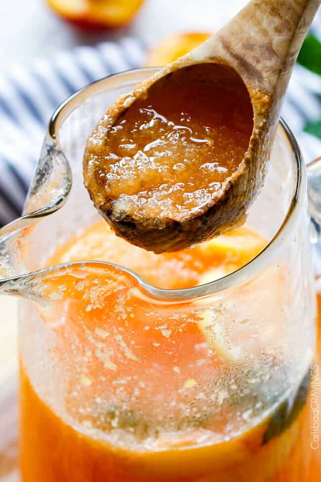 Close up of Sparkling Peach Punch in a pitcher and s wood spoon mixing it.