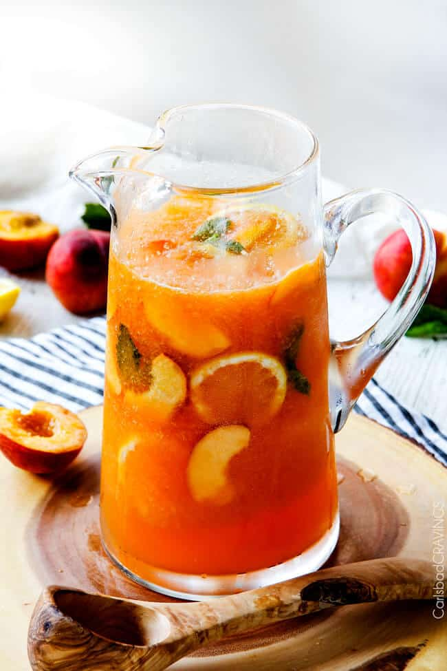 A full pitcher of Sparkling Peach Punch with oranges in the juice.