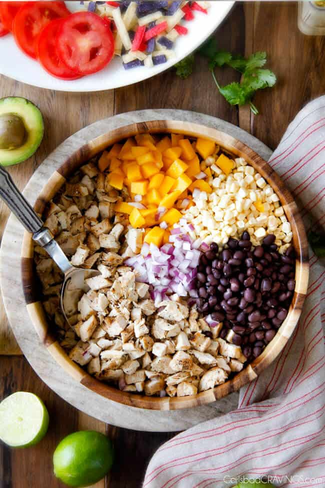 Showing how to make Avocado Chicken Salad by adding filling ingredients of chicken, mangos, corn, black beans, to a large wood bowl