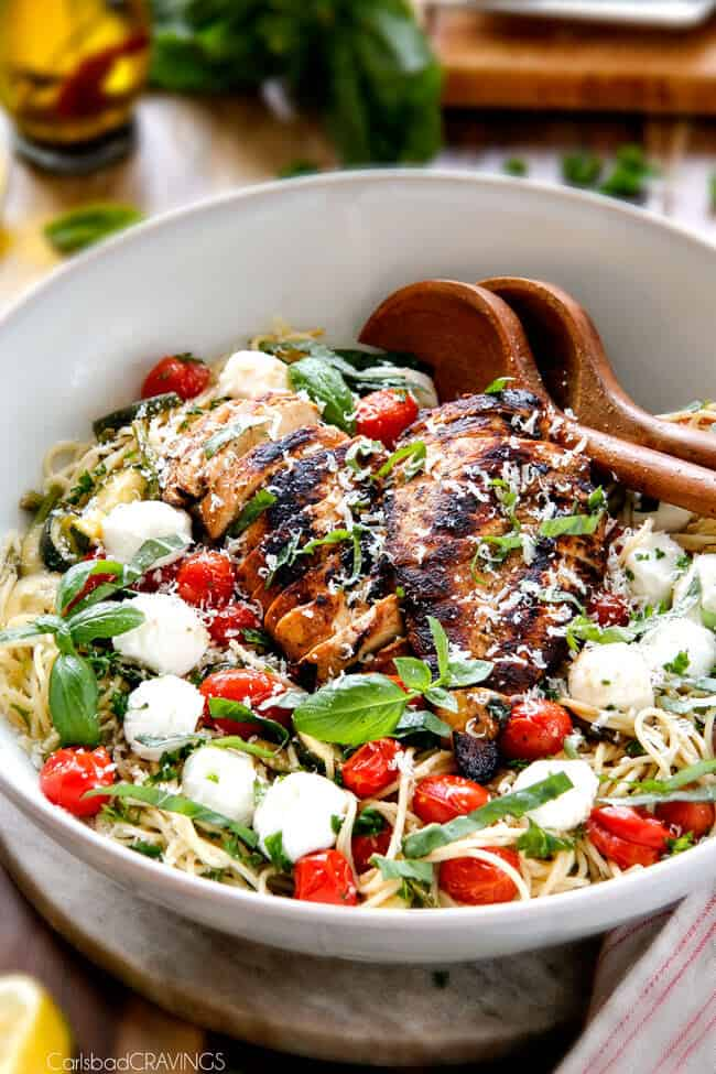 Caprese Chicken Pasta in a bowl with two wooden serving spoons cheese and tomatoes. .