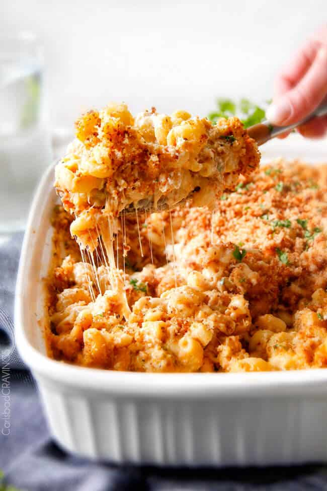 A cheesy scoop of Million Dollar Macaroni and Cheese coming out of a pan.