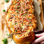 Mega flavorful Buffalo Chicken Dip Stuffed French Bread is your favorite cheesy dip baked right into the loaf! Crazy delicious side or EASY crowd pleasing appetizer! Everyone will be begging you to bring this!