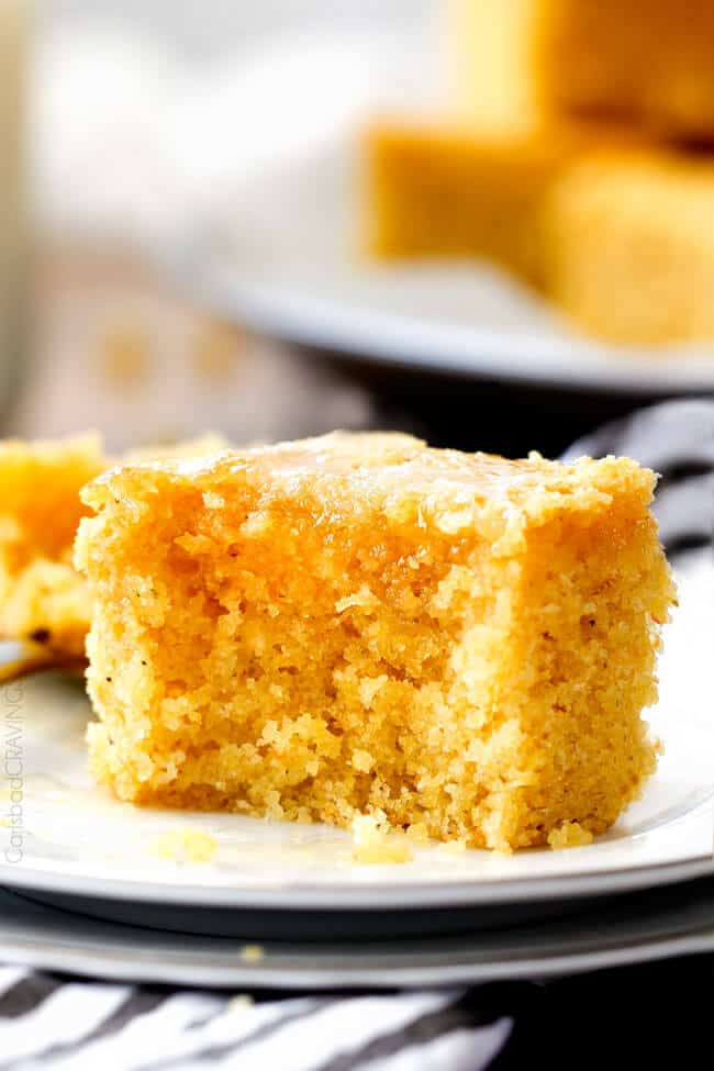 up close of a slice of Sweet Cornbread with a bite out of it on a white plate
