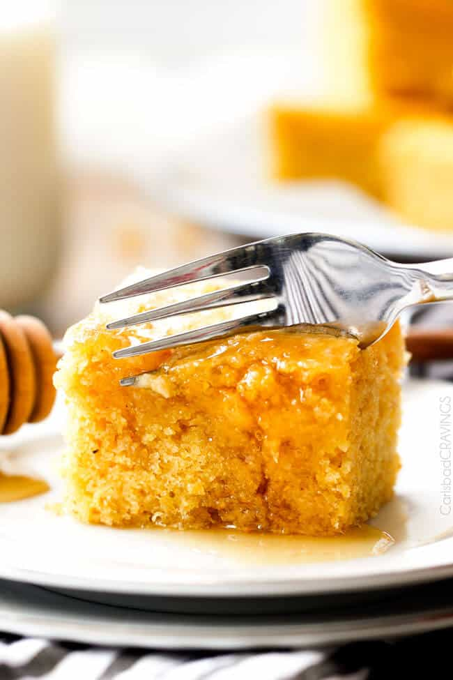 a fork slicing into Sweet Cornbread recipe smothered in honey