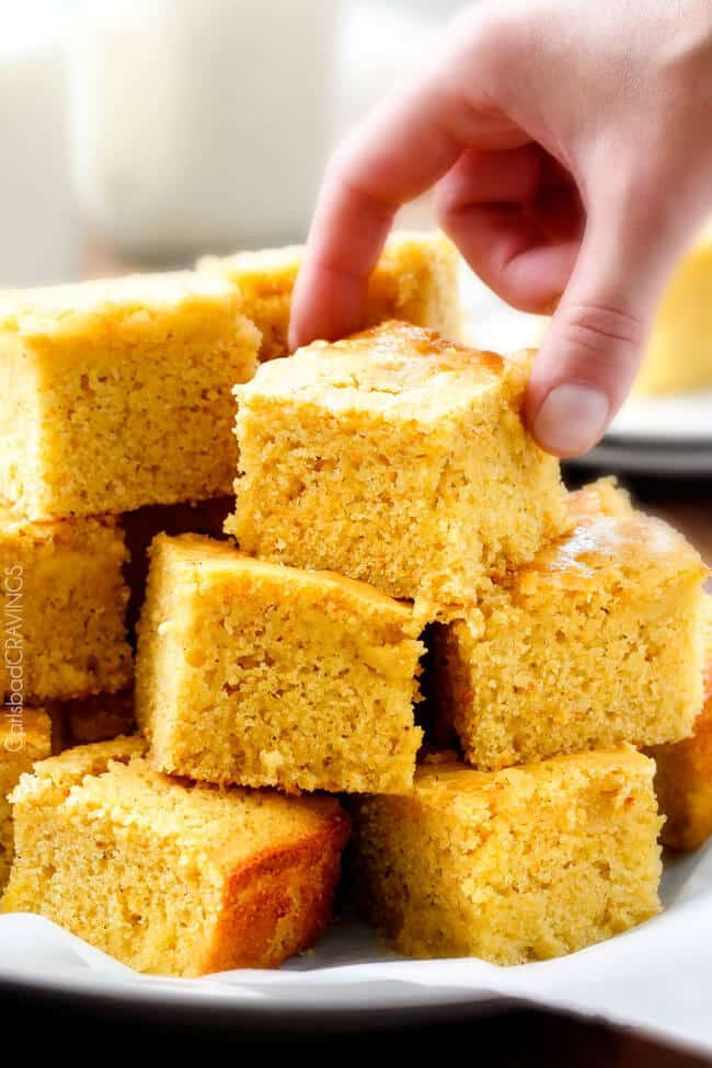 a hand picking up a slice of Sweet Cornbread stacked on a plate