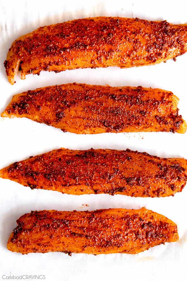 showing how to make Tilapia Fish Tacos by adding a wet spice rub all over the tilapia fillets