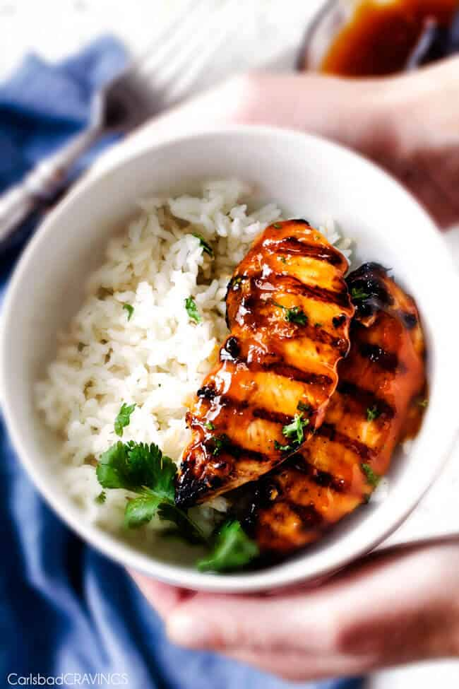 two pieces of grilled pineapple chicken on bed of rice in white bowl