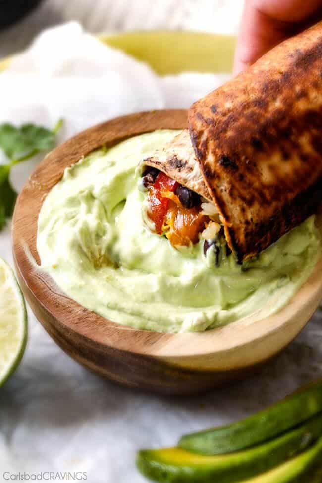 Chicken Fajita Wraps with Creamy Avocado Dip - layers of cheese, black beans, rice, the BEST chicken fajita filling, and sour cream all rolled up then skillet toasted for slightly crispy wraps that are absolutely addicting!! This is our family's favorite way to eat leftover chicken fajita filling!