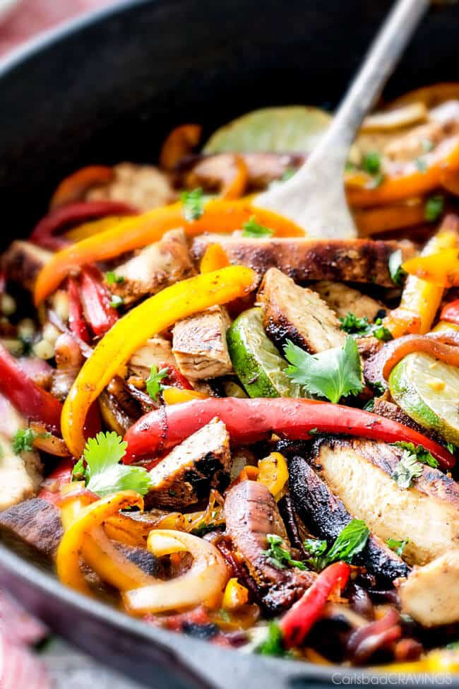 up close of chicken fajitas with sliced chicken, sliced bell peppers and sliced onions in cast iron skillet