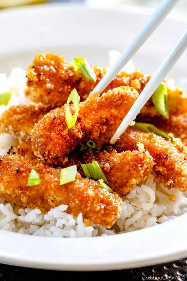 Crispy Chinese Lemon Chicken with green onion on top being picked up with chop sticks.