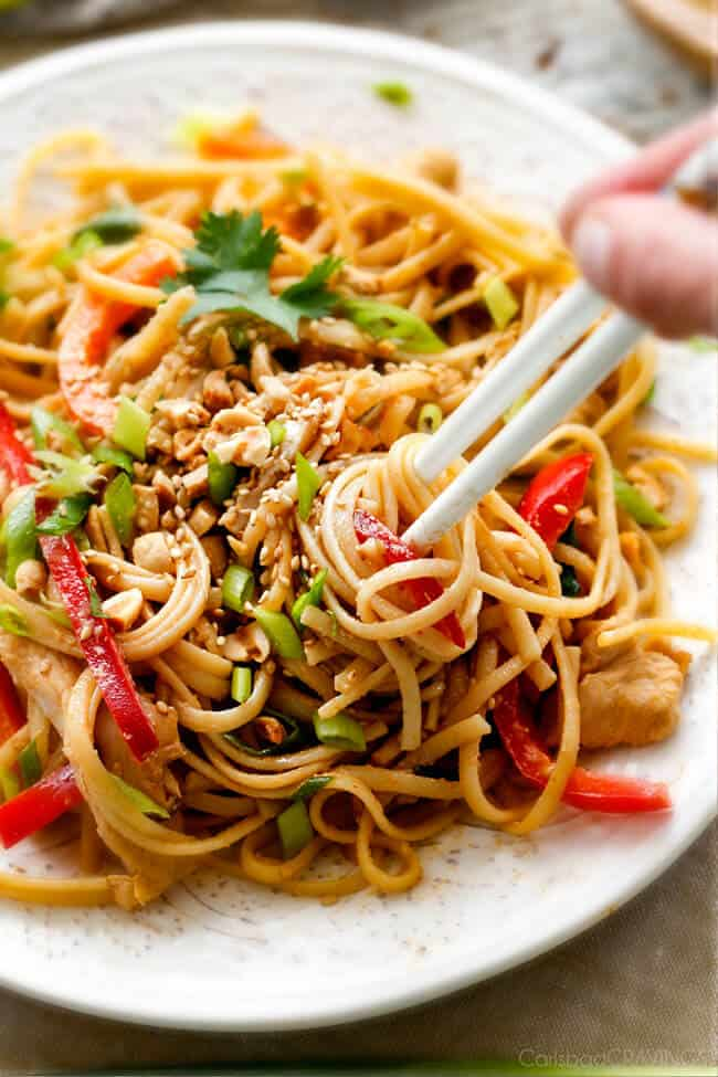 Chinese Sesame Noodles on a white plate with white chopsticks picking up noodles