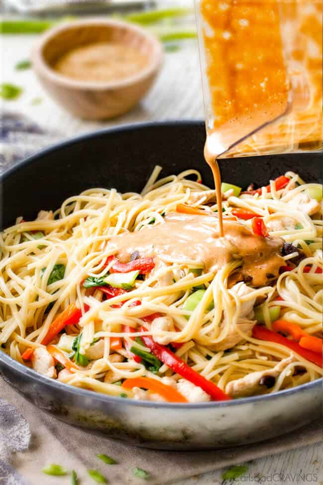 Pouring sesame sauce over noodle and vegetables to make Sesame Noodles