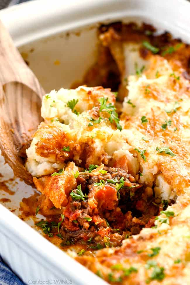 scooping out a serving of ultimate Shepherd's Pie from a casserole dish