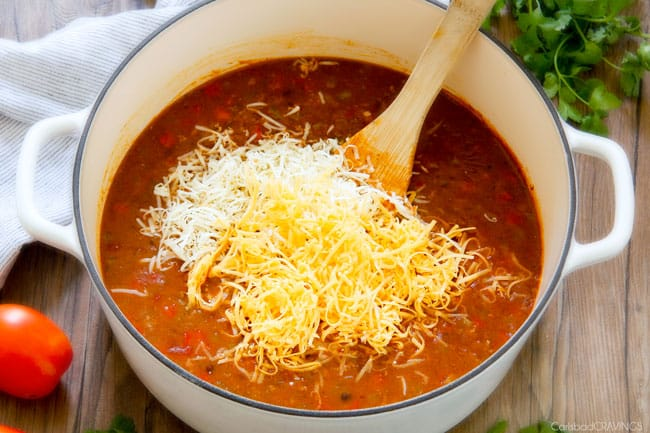 showing how to make cheesy taco soup by adding cheddar cheese to Taco Soup in white soup pot