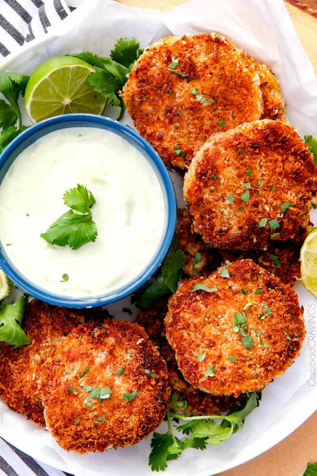 top view of best crab cake recipe with crab cake sauce in a white serving dish with lemon garnish