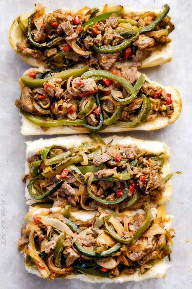 top view of authentic Philly Cheesesteak Sandwich recipe with the steak, bell peppers and cheese filling loaded on to hoagie buns