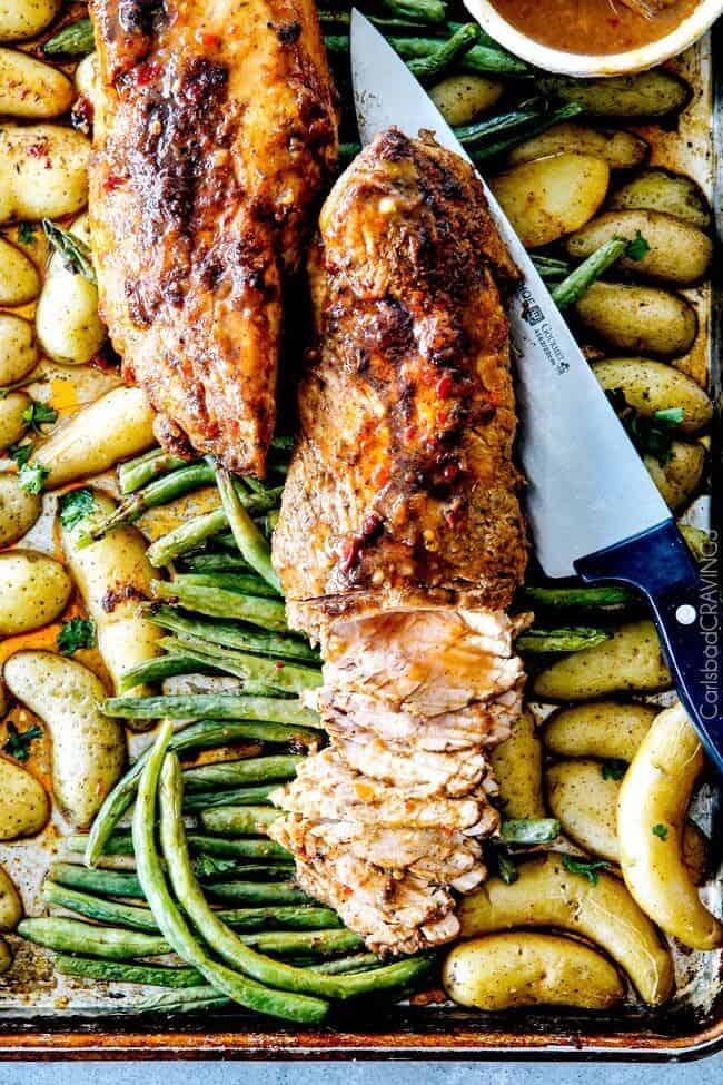 Pork Tenderloin over green beans on a sheet pan.