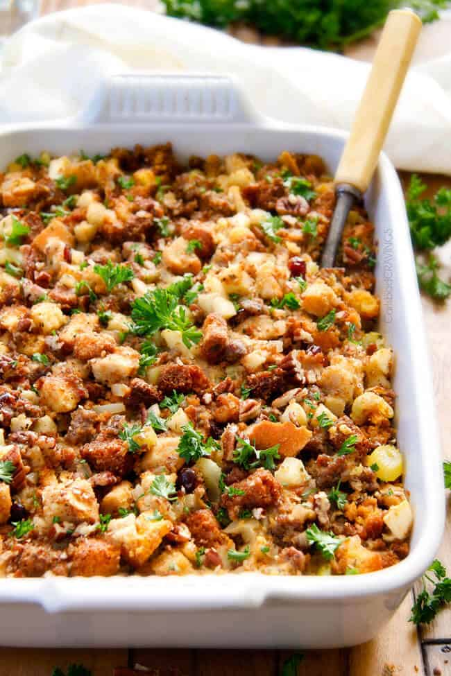 a white casserole dish of Thanksgiving Cornbread Sausage Stuffing garnished with parsley