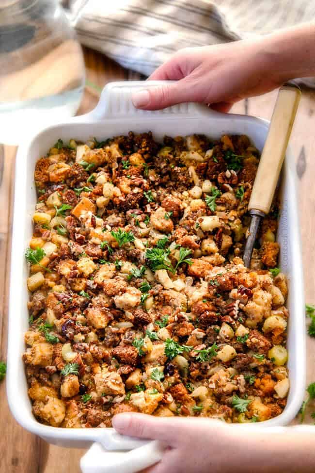 two hand holding a white casserole dish of the best Cornbread Stuffing with sausage