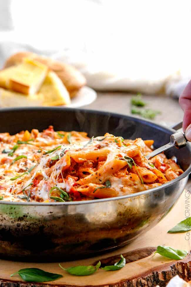 Cheesy Penne & New York Bakery® Bake Garlic Bread in a pan serving with a spoon.