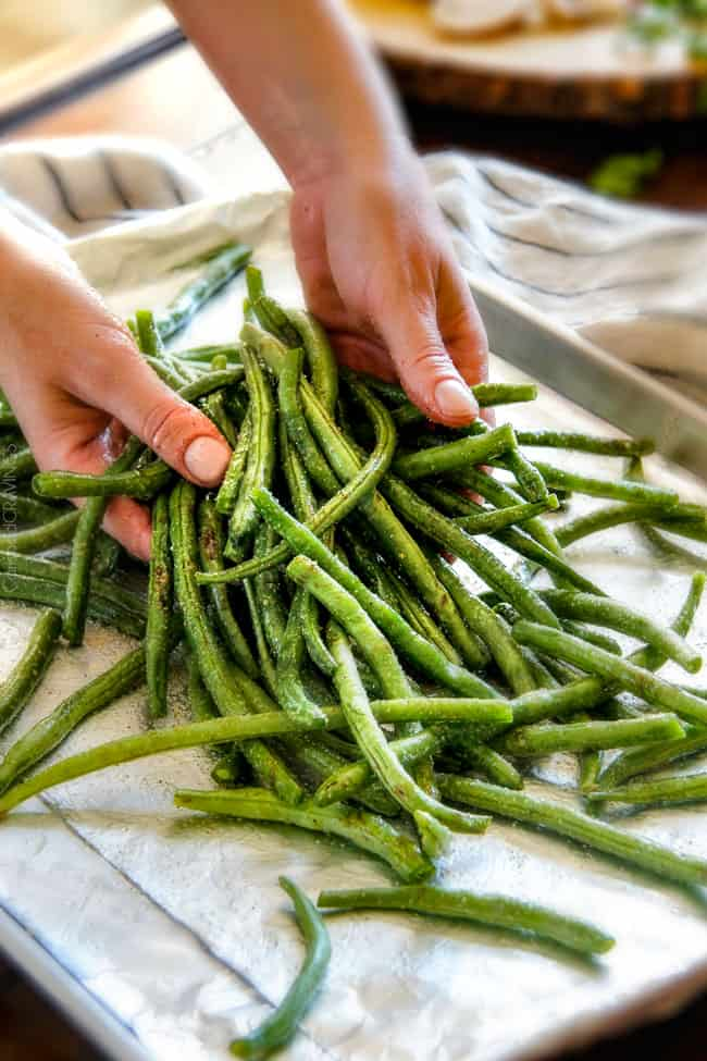 Showing how to make Roasted Green Beans with Bacon by tossing green beans with olive oil salt and pepper on a baking sheet