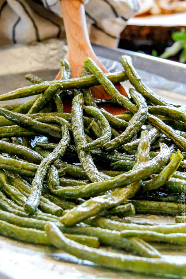 Showing how to make Roasted Green Beans with Bacon by stirring green beans on the baking sheet