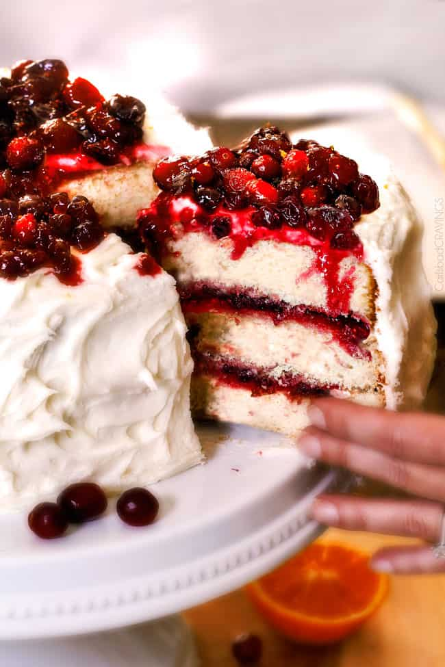 A layered cranberry cake with a slice of cake being served.