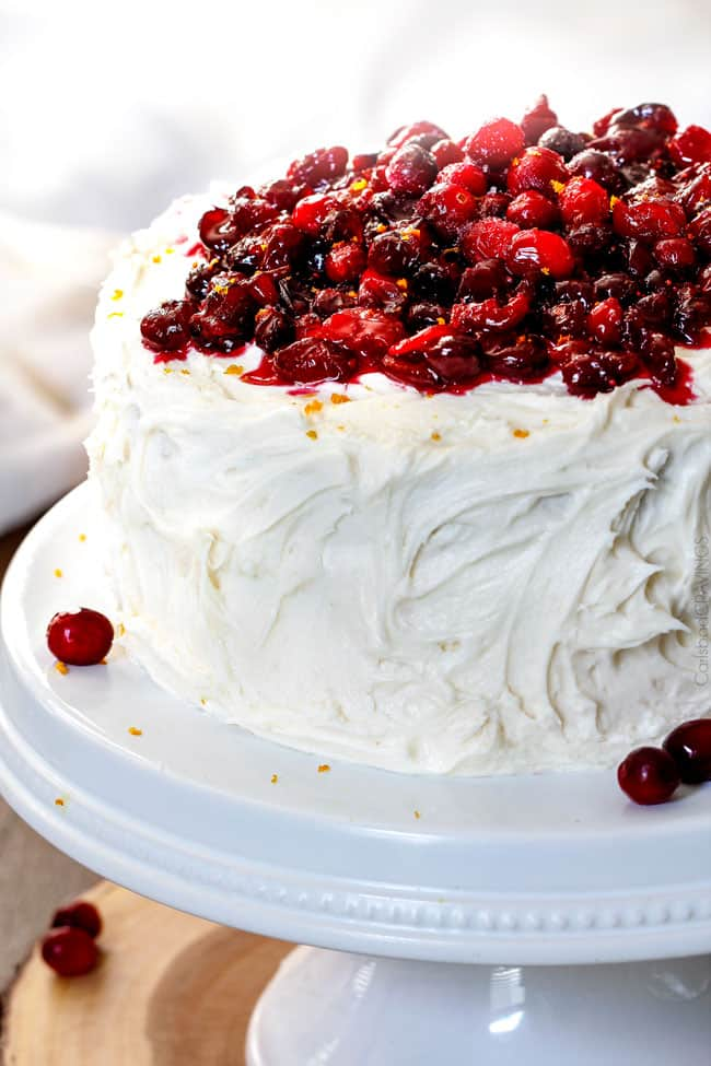 White Cake with Cranberry Filling and Buttercream Frosting – everyone always asks me for this recipe! The moist, bakery style white cake is the BEST ever and the sweet and tangy cranberry filling is melt in your mouth delicious and Christmas festive!