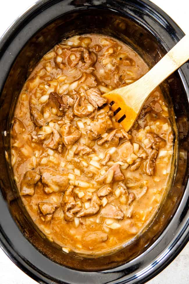 showing how to make easy Slow Cooker Beef Stroganoff by stirring together gravy, meat, onions and mushrooms in a black cork pot with a wooden spoon