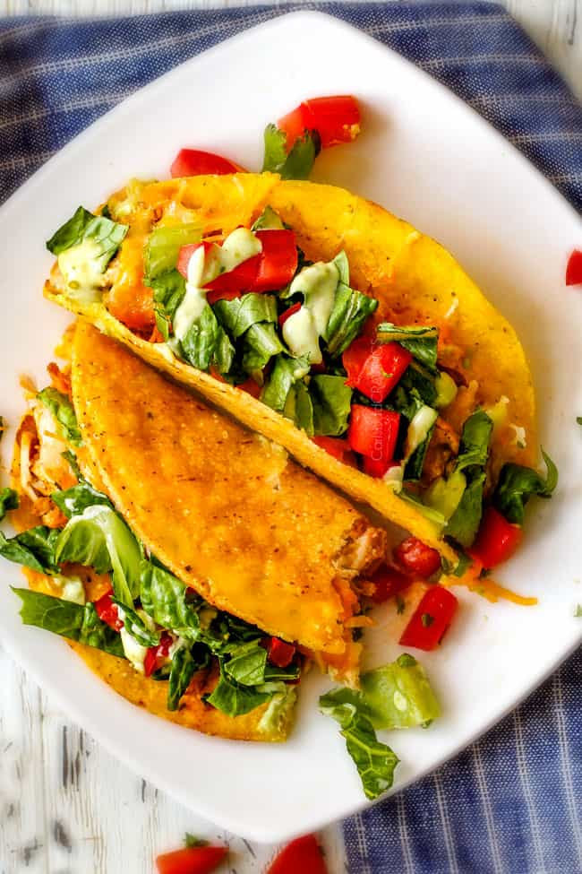 EASY Baked Fiesta Ranch Chicken Tacos piled with refried beans, cheese and the most amazing slow cooker chicken making assembly a snap! My family begs for these tacos weekly! And don't skip the Tomatillo Avocado Ranch - its to die for!
