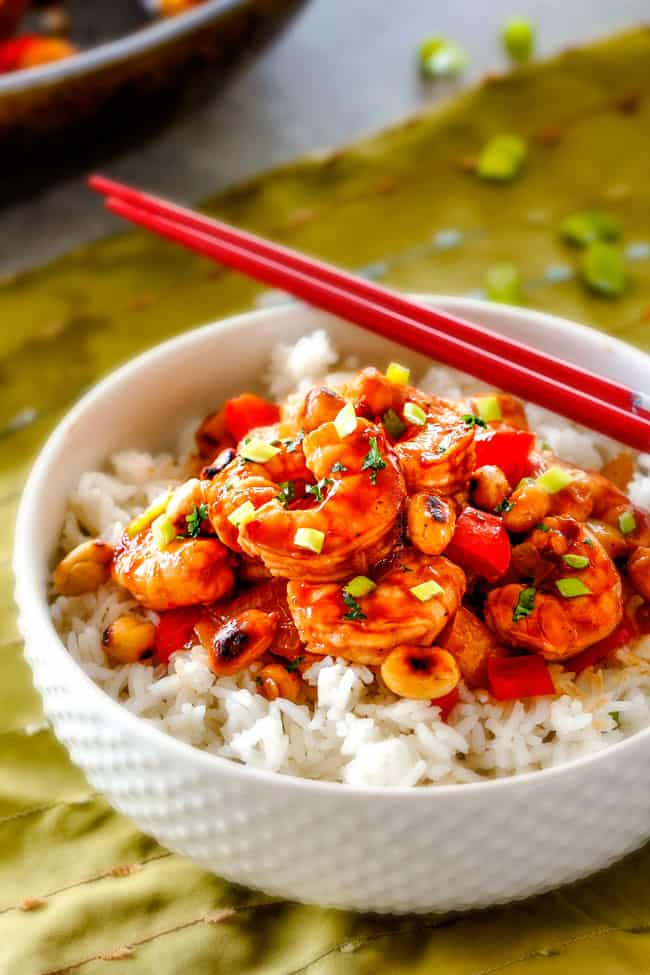 a white bowl full of rice and easy Kung Pao Shrimp with peanuts and green onions and red chopsticks
