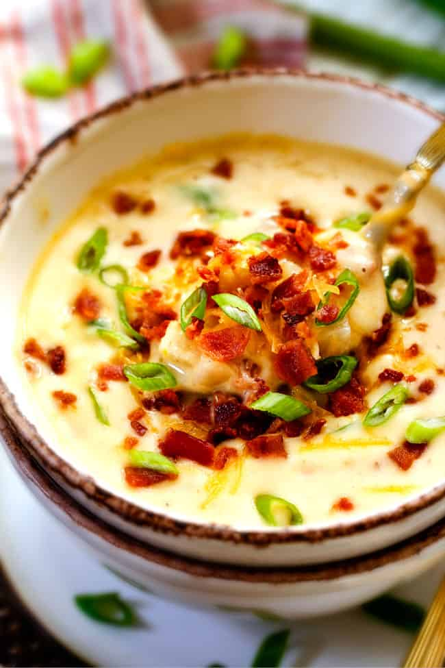 a spoonful of thick and creamy skinny crockpot potato soup with cheese, bacon and green onions