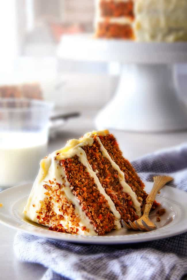 A slice of moist Carrot Cake with Cream Cheese Frosting on a white plate with carrot cake in the background on a cake stand