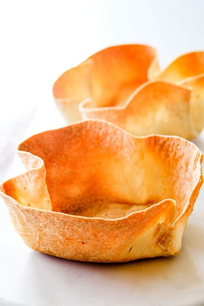 showing how to make tortilla bowls to serve taco salad by baking until crispy