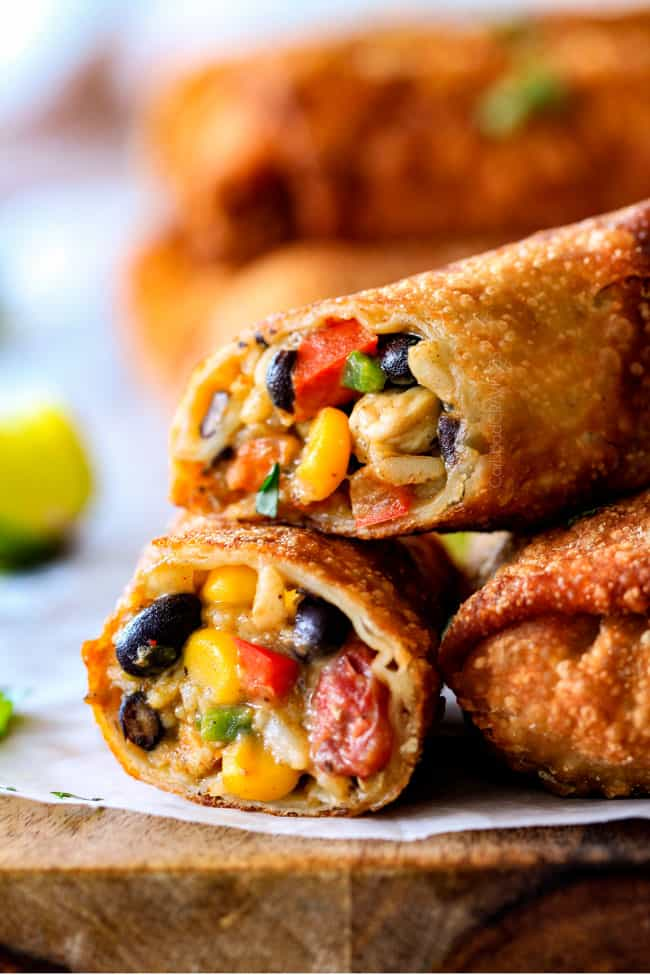 up close of open Southwest Egg Rolls oozing with cheesy filling with avocado, chicken, tomatoes, corn and black beans
