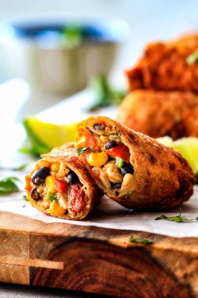 crispy southwest egg rolls leaning next to each other filled with chicken, cheese, corn, black beans, tomatoes and avocao
