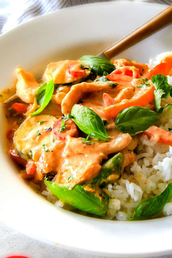 Close up of Thai Red Curry Chicken with rice and chop sticks.