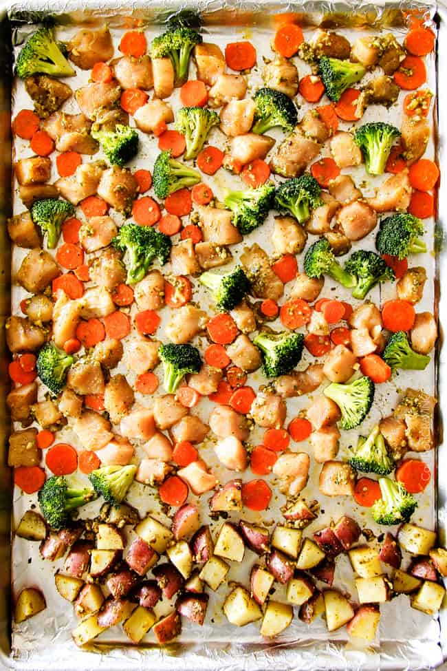 Showing how to make Sheet Pan Parmesan Pesto Chicken with Potatoes, Broccoli and Carrots by baking it on a sheet pan.
