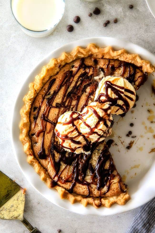 top view of cookie pie with premade dough in a white pie pan, topped with ice cream, caramel and chocolate sauce