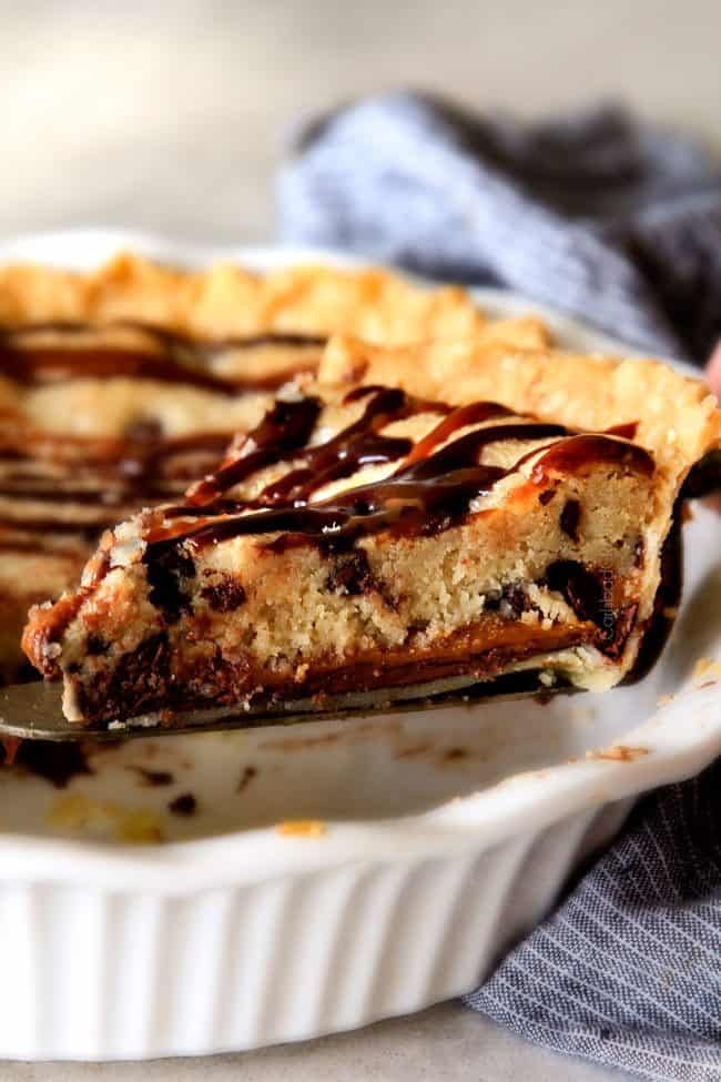 taking out a slice of gooey chocolate chip cookie pie with a pie server