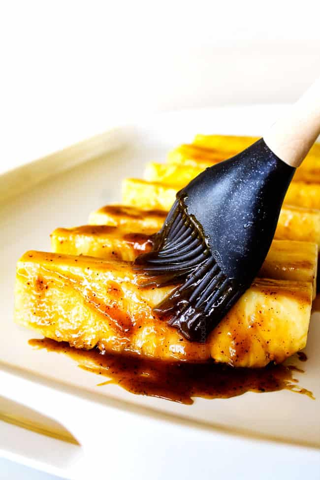 showing how to make Grilled Pineapple by brushing pineapple with glaze
