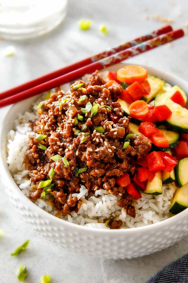 side view of Korean Beef with Veggies in a white bowl with red chopsticks