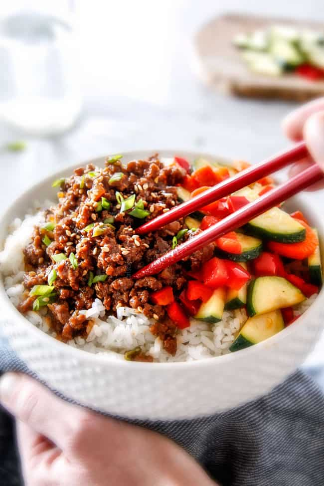 chopsticks taking a bite of ground beef from a Korean Beef Bowl with Veggies