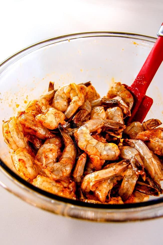 showing how to make Old Bay Shrimp by marinating with cocktail sauce in a glass bowl
